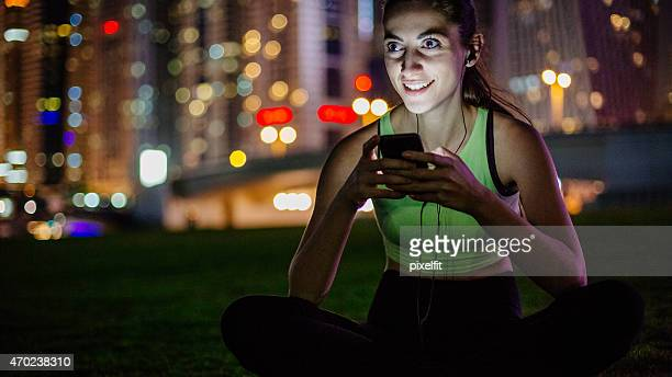 Woman with headphones and skyline background in the night
