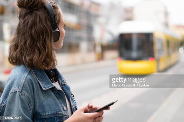 woman with headphones and smart phone standing in city - transporte público imagens e fotografias de stock