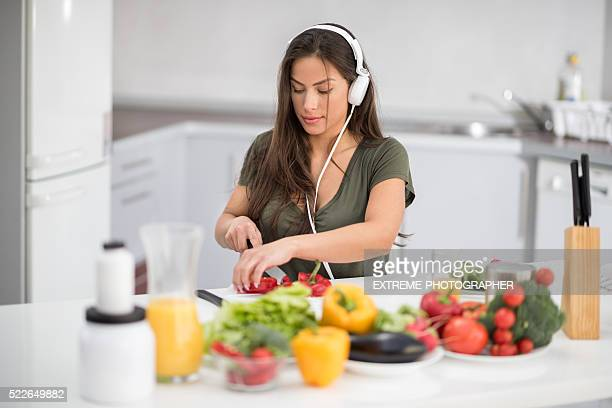 woman with headphones cutting bell pepper - mp3 juices stock photos and pictures