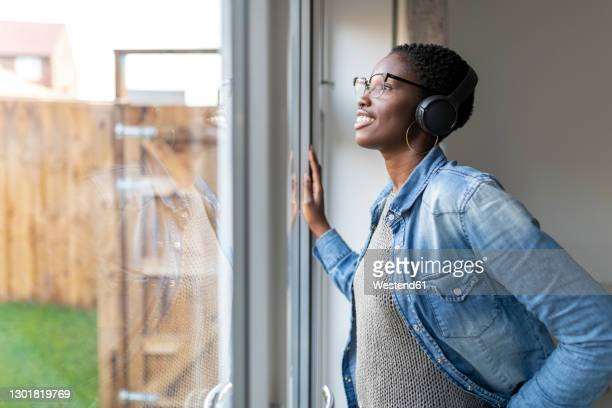 woman with headphones looking through window - looking through window stock pictures, royalty-free photos & images