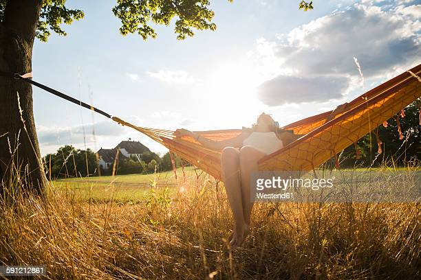 Woman with headphones lying in a hammock relaxing in nature