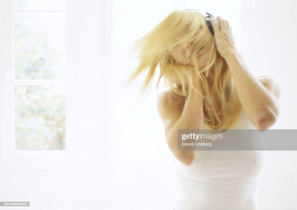 Woman with headphones on, shaking head, inside. : Stockfoto