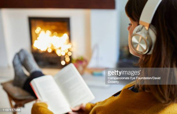 woman with headphones reading in living room - boek stockfoto's en -beelden