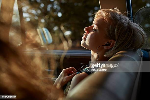 woman with headphones relaxing in car, at sunset - musica foto e immagini stock