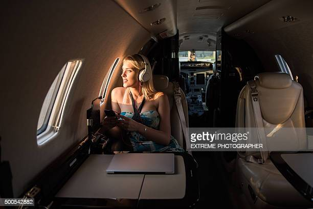 Woman with headphones sitting inside private jet airplane