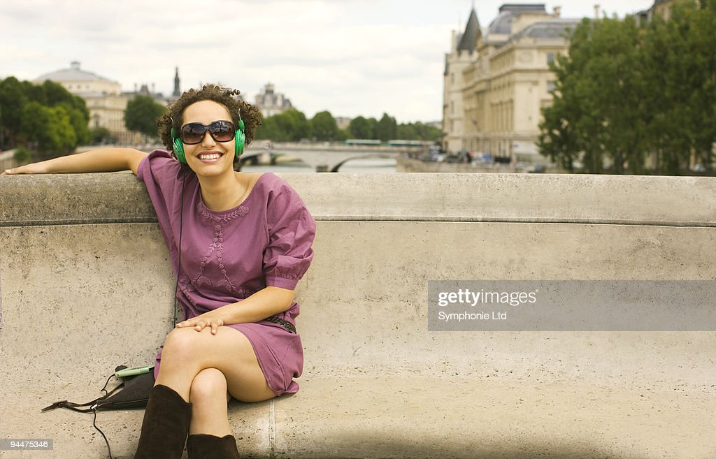 Woman with headphones sitting on bench : Stock Photo