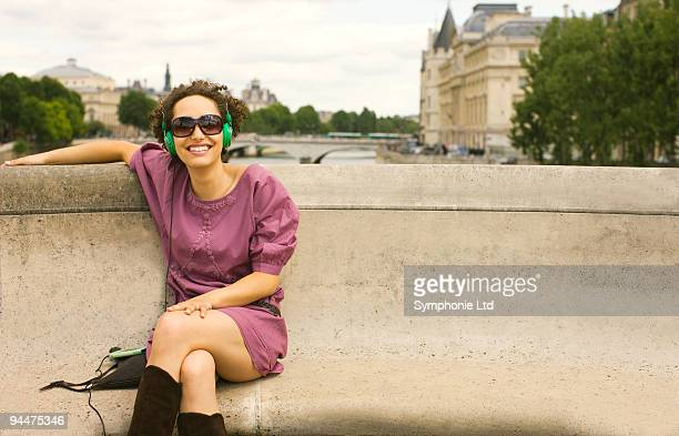 Woman with headphones sitting on bench