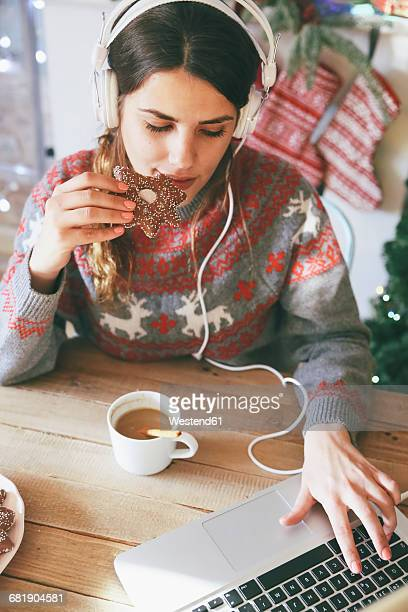 Woman with headphones using laptop while eating Christmas cookie