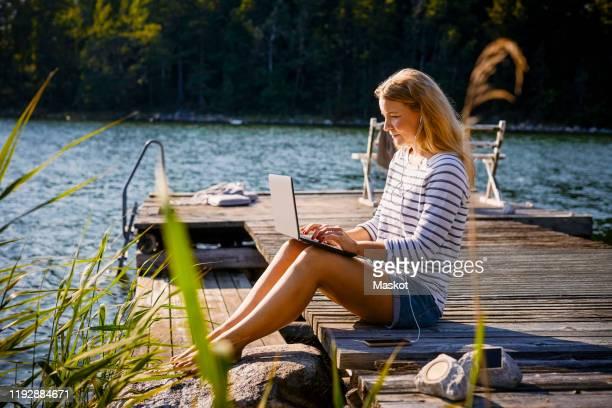 woman with headphones using laptop while sitting on jetty against lake - gemak stockfoto's en -beelden