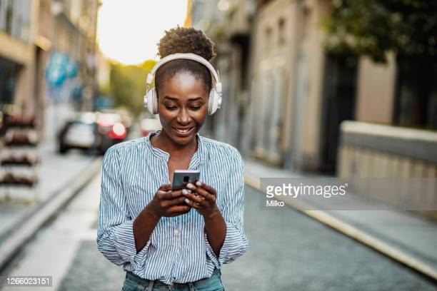 woman with headphones using phone on the street - listening stock pictures, royalty-free photos & images