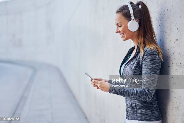 woman with headphones using smartphone - mood stream stock pictures, royalty-free photos & images