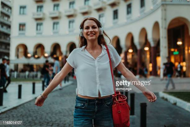 woman with headphones walking in the city street - thessaloniki stock pictures, royalty-free photos & images