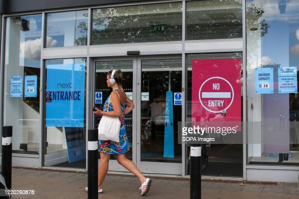 Woman with headphones walks past a branch of Next store in north London.