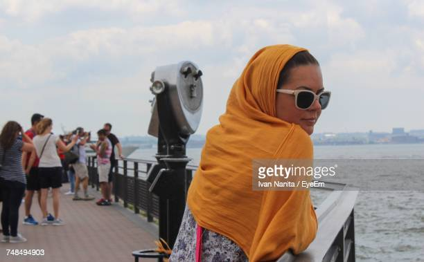 Woman With Headscarf And Sunglasses Leaning On Railing At Liberty Island Against Sky