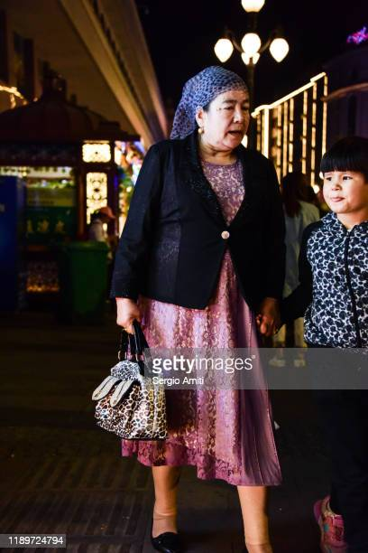 woman with headscarf at a night market in urumqi - sergio amiti stock pictures, royalty-free photos & images