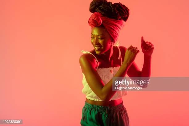 woman with headscarf dancing against peach background - solo una donna giovane foto e immagini stock