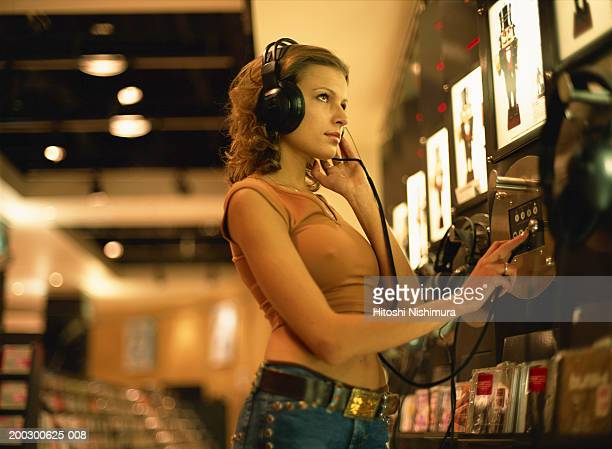 Woman with headset at record store, side view