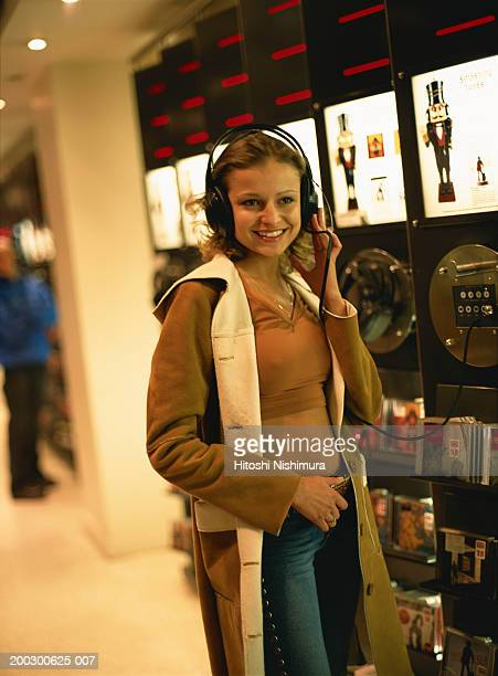 Woman with headset at record store, smiling