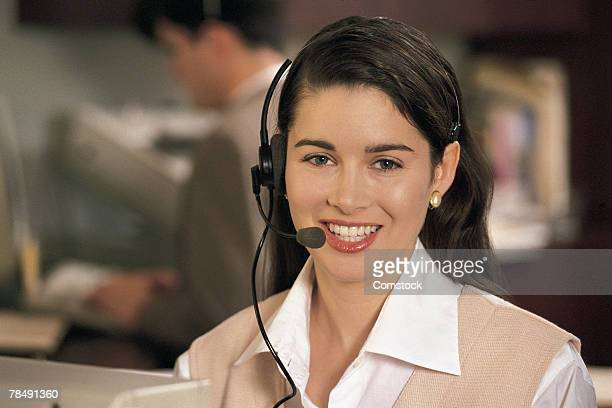 woman with headset in office with others - category:cs1_maint:_others stock pictures, royalty-free photos & images