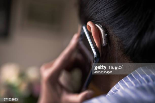 woman with hearing aid talking via cell phone - ear stock pictures, royalty-free photos & images