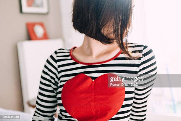 Woman With Heart Shape On T-Shirt At Home