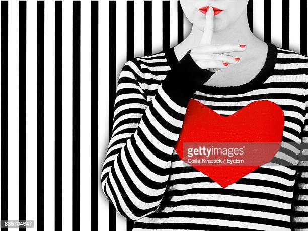 Woman With Heart Shape On T-Shirt Standing Against Striped Wall