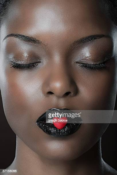 woman with heart shaped candy in mouth - valentines african american stock pictures, royalty-free photos & images