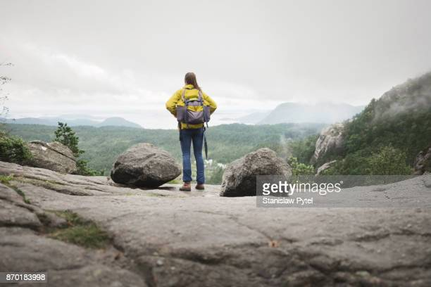 Woman with hellow backpack admiring mountain view