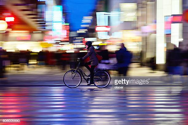 Woman with helmet, biking in night Stockholm