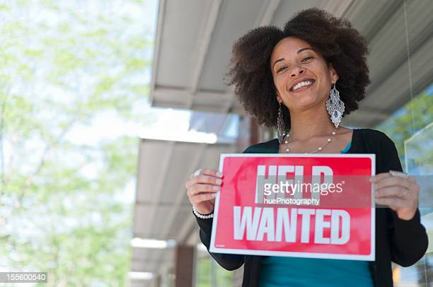 woman with help wanted sign - help wanted sign stock photos and pictures