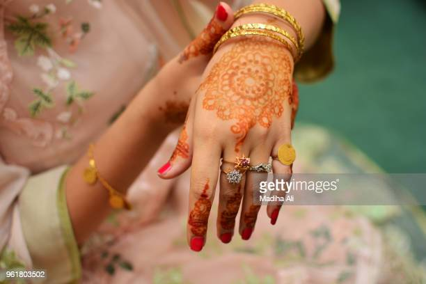 a woman with henna tattoo and jewelery on her hands - pakistani gold jewelry stock pictures, royalty-free photos & images