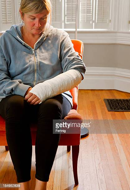 Woman with her arm in a cast at home alone.