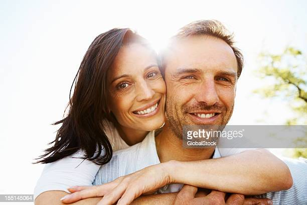 woman with her arms wrapped around her man - falling in love stock pictures, royalty-free photos & images