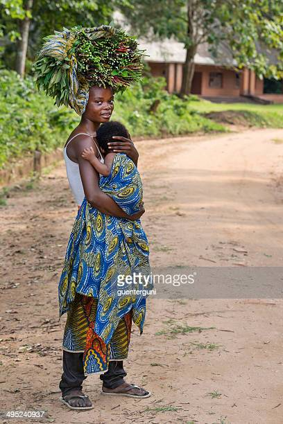 Woman with her baby carrying vegetables