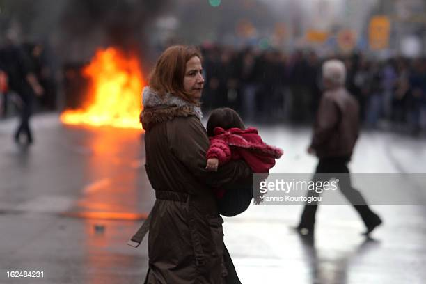 A woman with her baby cross the road while demonstrators set on fire dumpsters in Thessaloniki on December 62011
