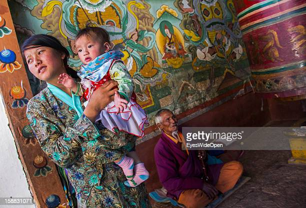 A woman with her baby in the monastery in the village Chimi Lhakhang in the Punakha Valley with its temple monastery is renowned for its fertility...