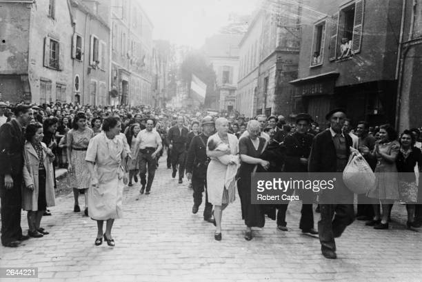 A woman with her baby whose father is German and her mother are jeered and humiliated by crowds in Chartres after having their heads shaved as...
