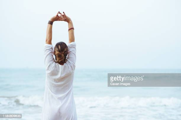 woman with her back and white dress doing stretching on the beach. - weißes kleid stock-fotos und bilder