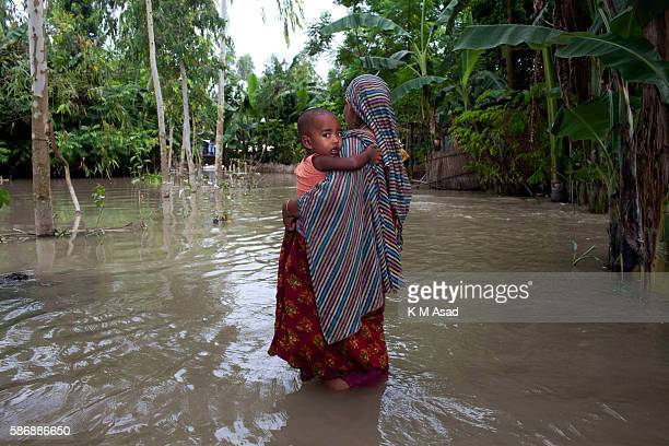 Woman with her child going to take relief aid in the floodwater at Kurigram Bangladesh has been suffering from devastating monsoon floods from the...