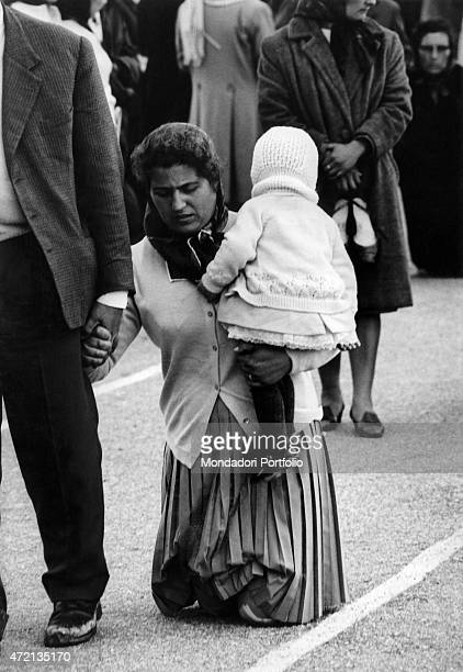 'A woman with her child in her arms going on her knees in the square of Sanctuary of Fatima on the occasion of the 100th anniversary of the...