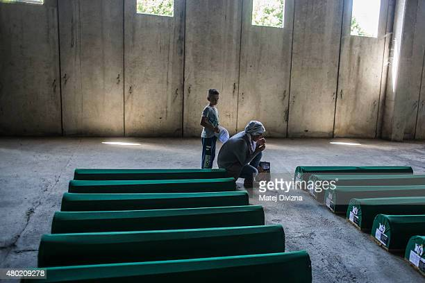 A woman with her child mourns over a coffin among 136 coffins of victims of the 1995 Srebrenica massacre in the hall at the Potocari cemetery and...