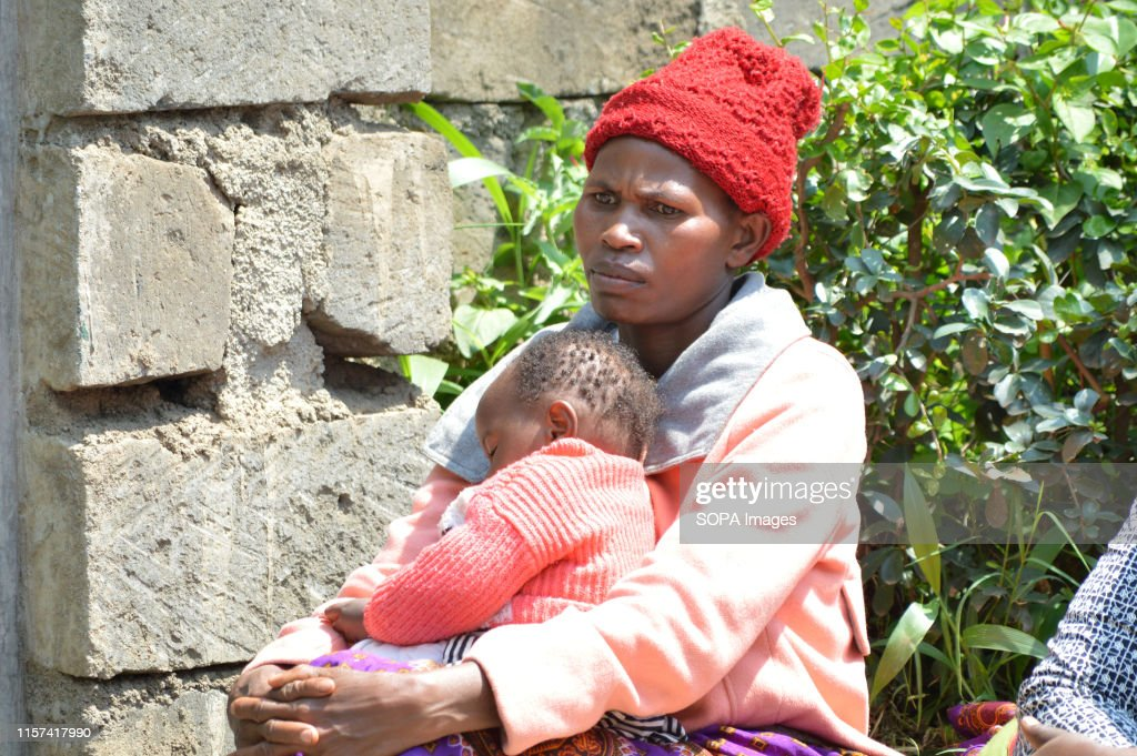A woman with her child seen in thought after hearing of the... : News Photo