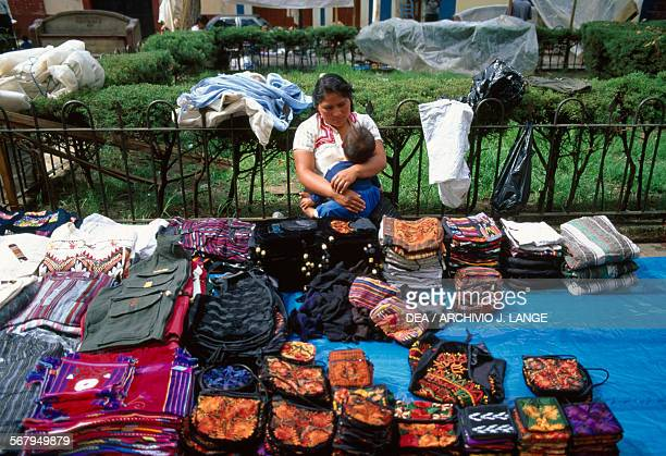 A woman with her child selling fabric and bags in San Cristobal de Las Casas market Chiapas Mexico