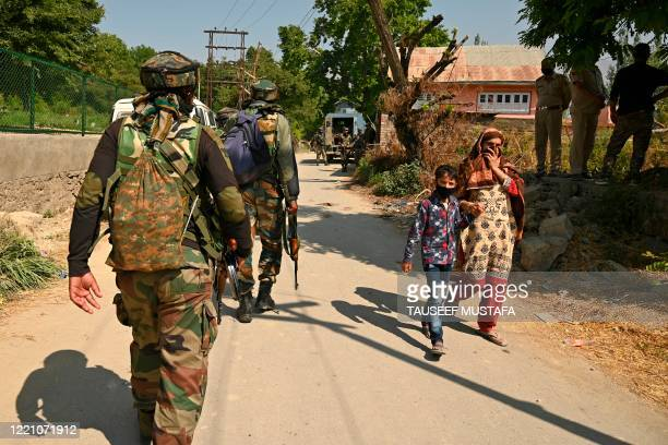 Woman with her child walks past Indian army soldiers near a mosque at the site of a gunbattle at Meej Pampore area of Pulwama district, south of...