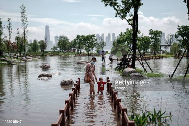 Woman with her child wear a mask while walking through the flooded Jiangtan park damaged by heavy rains along the Yangtze river on July 8th, 2020 in...