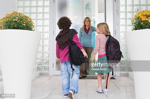 Woman with her children at the entrance door of a house