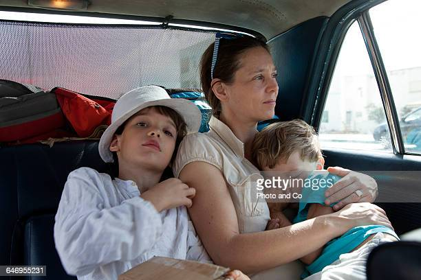 woman with her children in a car