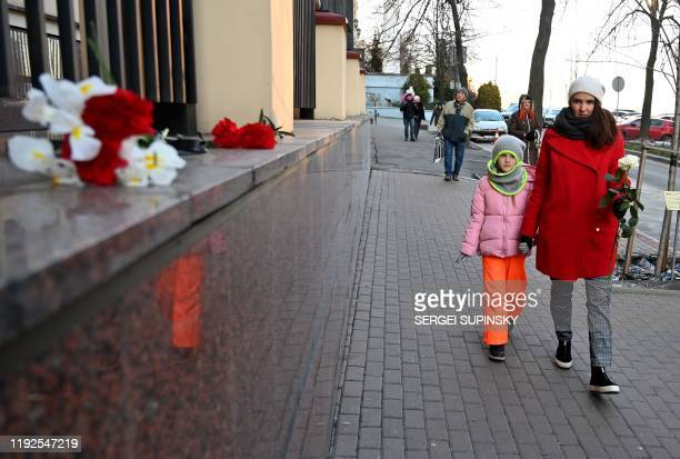 A woman with her daughter arrive to lay flowers outside the Canadian Embassy in Kiev on January 8 2020 in remembrance of the victims of the Ukraine...