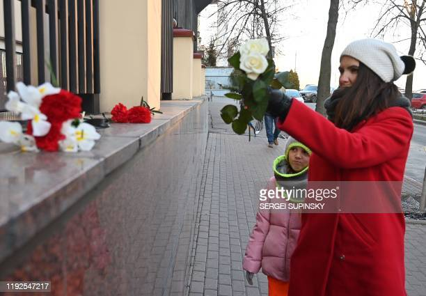 A woman with her daughter lay flowers outside the Canadian Embassy in Kiev on January 8 2020 in remembrance of the victims of the Ukraine...