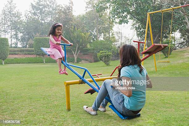 woman with her daughter playing on a seesaw - biciancola foto e immagini stock